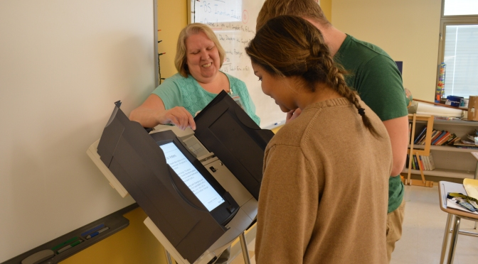 Seniors Samara Warren and Brian Stein learn how to cast votes from the League of Women Voters.